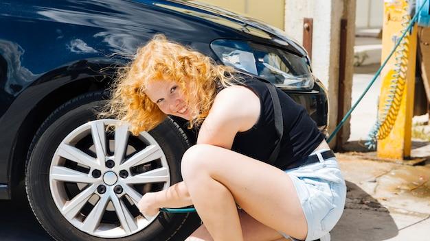 Junge frau, die reifen des autos an der tankstelle am sonnigen sommertag aufpumpt Kostenlose Fotos