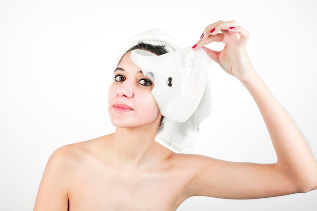 Junge frau, die reinigungsmaske von ihrem gesicht entfernt Kostenlose Fotos