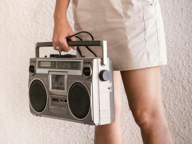 Junge frau, die retro- musikspieler hält Kostenlose Fotos