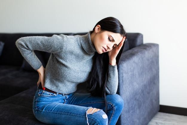 Junge frau, die rückenschmerzen leidet und sich beschwert, auf einer couch im wohnzimmer zu hause zu sitzen Kostenlose Fotos
