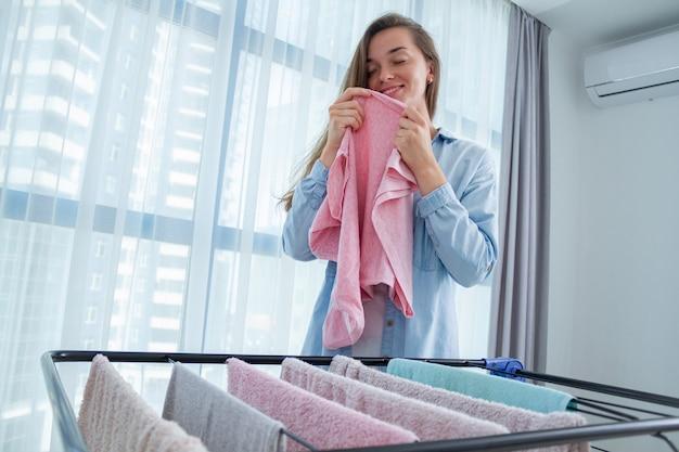 Junge frau, die saubere wäsche nach wäsche zu hause riecht. wäschetrockner nach dem waschen verwenden. hausarbeit und haushalt Premium Fotos