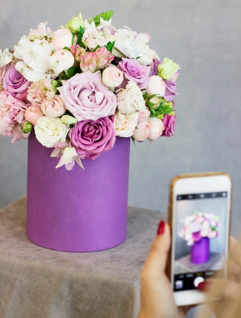 Junge frau, die schönen blumenstrauß im purpurroten kasten schießt Premium Fotos
