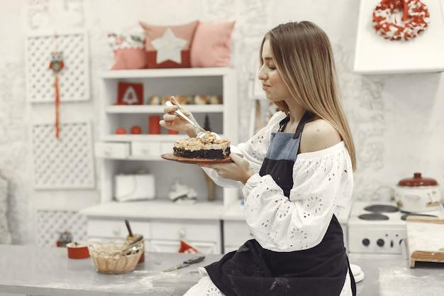 Junge frau, die selbst gemachten kuchen in der küche hält Kostenlose Fotos
