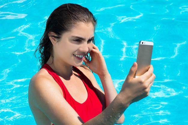 Junge frau, die selfie am swimmingpool nimmt. Premium Fotos