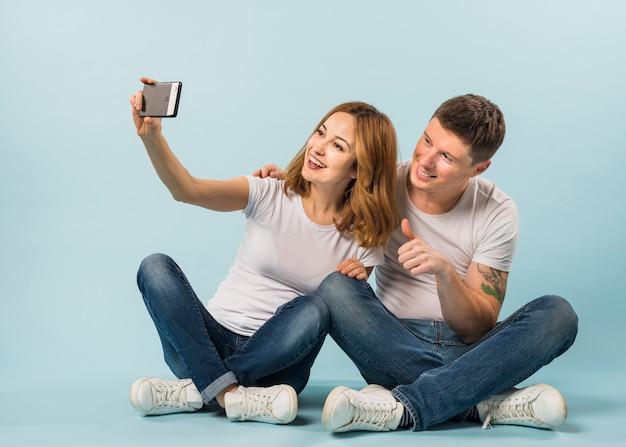 Junge frau, die selfie mit ihrem freund zeigt daumen herauf zeichen nimmt Kostenlose Fotos