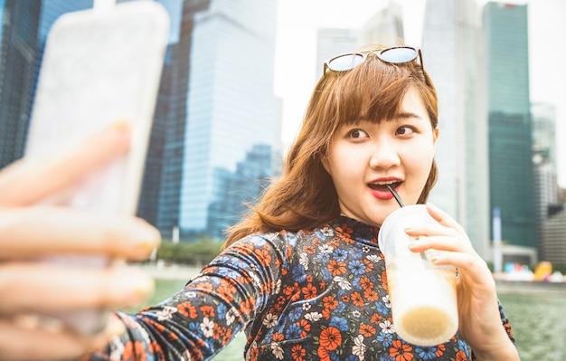 Junge frau, die selfie mit kaffee in singapur nimmt Premium Fotos