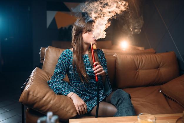 Junge frau, die shisha im restaurant raucht Premium Fotos