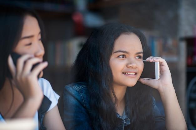 Junge frau, die smartphone mit dem fühlen glücklich verwendet und betrachtet Kostenlose Fotos