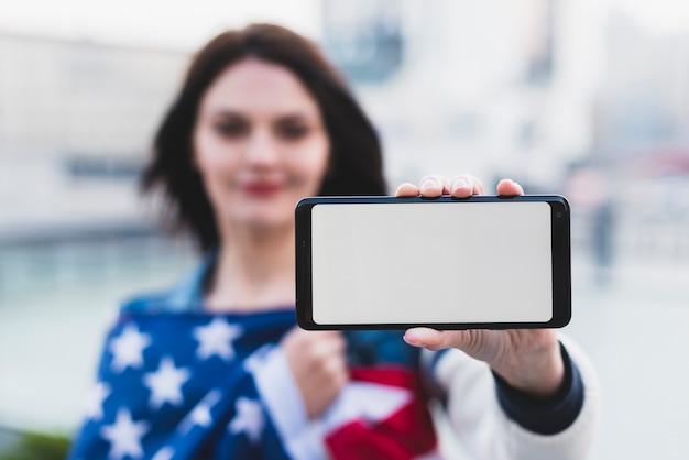 Junge frau, die smartphone mit leerem bildschirm zeigt Kostenlose Fotos