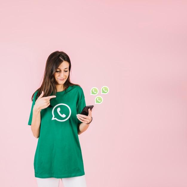 Junge frau, die smartphone nahe whatsapp ikone hält Kostenlose Fotos