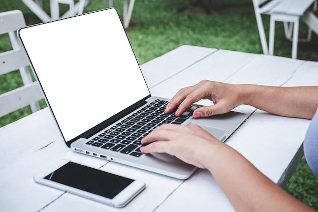 Junge frau, die smartphone zum kontakt der arbeit, durchdachter unternehmer anschließt an computer hält Premium Fotos