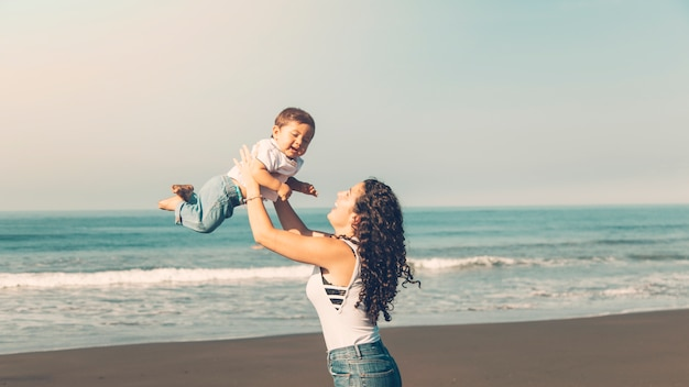 Junge frau, die spaß mit baby auf sommerstrand hat Kostenlose Fotos