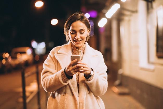 Junge frau, die telefon außerhalb der nachtstraße verwendet Kostenlose Fotos