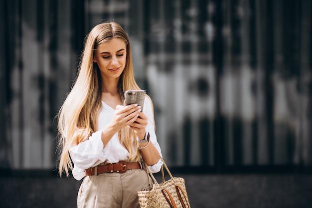 Junge frau, die telefon heraus in der stadt verwendet Kostenlose Fotos