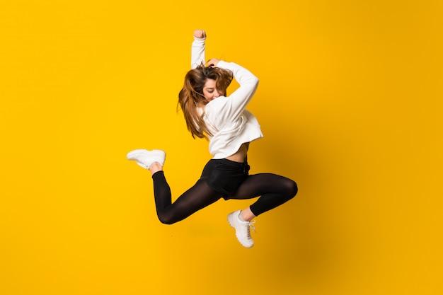 Junge frau, die über lokalisierte gelbe wand springt Premium Fotos