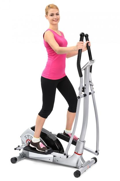 Junge frau, die übungen auf elliptischem trainer tut Premium Fotos