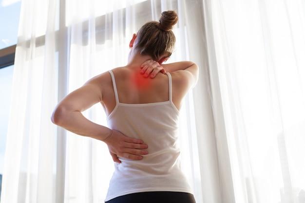 Junge frau, die unter nackenschmerzen und rückenschmerzen leidet und die muskeln zu hause streckt. rücken- und nackenschmerzen frau Premium Fotos