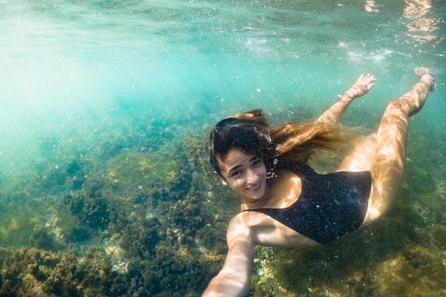Junge frau, die unter wasser selfie nimmt Kostenlose Fotos