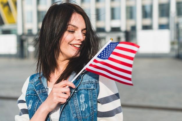 Junge frau, die usa-flagge am vierten juli wellenartig bewegt Kostenlose Fotos