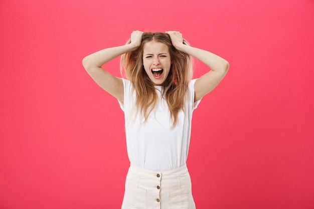 Junge frau, die verärgert, verrückt und schreien lokalisiert auf einem rosa hintergrund erhält. Premium Fotos