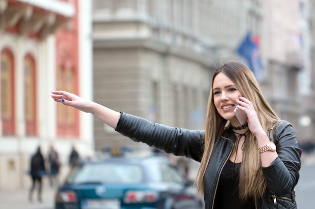 Junge frau, die versucht, ein taxi zu fangen Premium Fotos