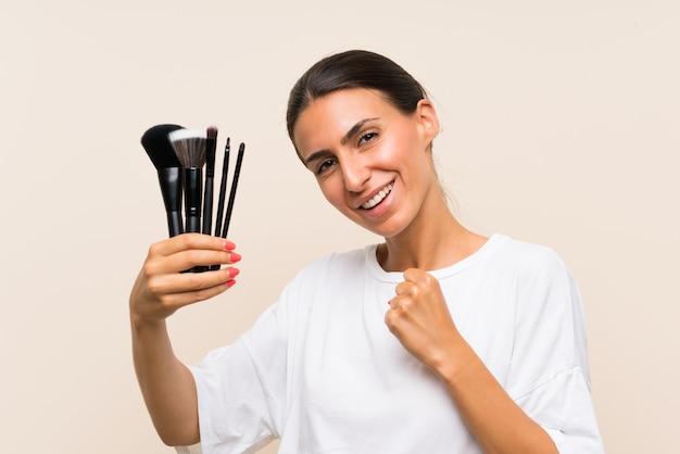 Junge frau, die viel make-upbürste feiert einen sieg hält Premium Fotos