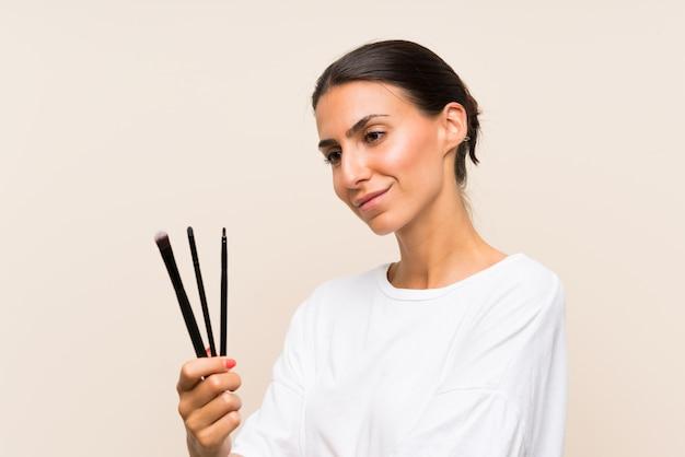 Junge frau, die viel make-upbürste hält Premium Fotos