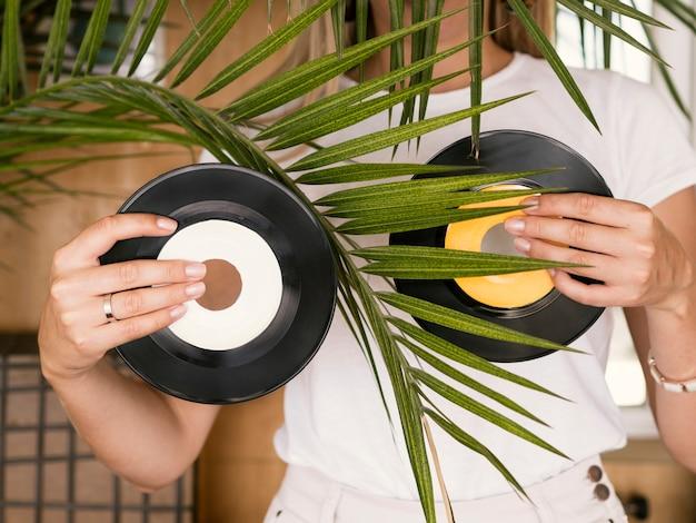 Junge frau, die vinylaufzeichnungen in beiden händen hinter anlage hält Kostenlose Fotos