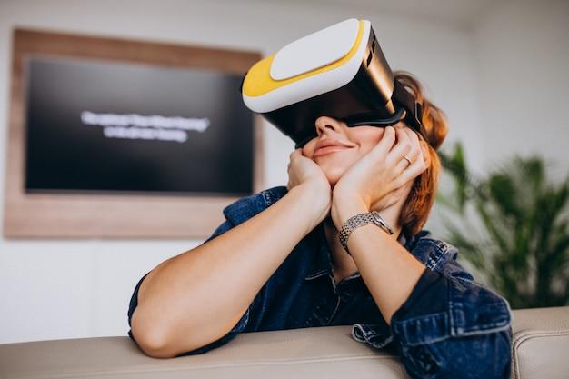 Junge frau, die vr gläser trägt und virtuelles spiel aufpasst Kostenlose Fotos