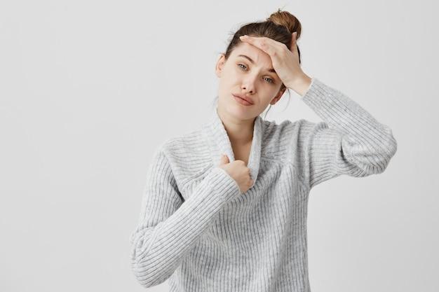 Junge frau, die warmen wollpullover trägt, der heiß ist und ihren kopf berührt, der versucht, sich auszuziehen. weibliche seo-spezialistin, die das gefühl hat, keine frische luft zu haben, drückt unzufriedenheit aus. sensationskonzept Kostenlose Fotos