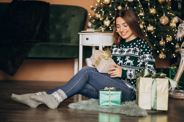 Junge frau, die weihnachtsgeschenk durch den weihnachtsbaum auspackt Kostenlose Fotos