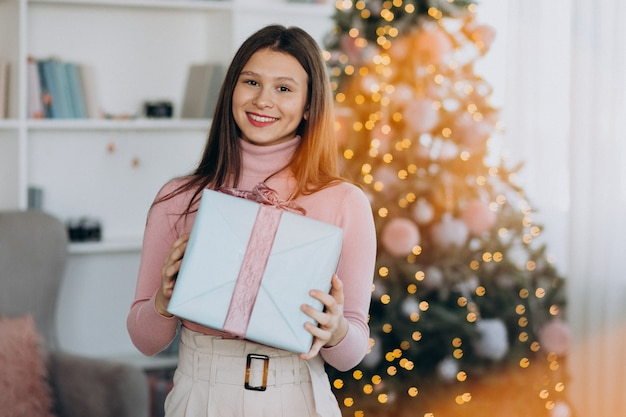 Junge frau, die weihnachtsgeschenk durch weihnachtsbaum hält Kostenlose Fotos