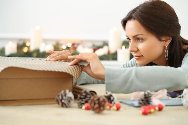 Junge frau, die weihnachtsgeschenk einwickelt Kostenlose Fotos