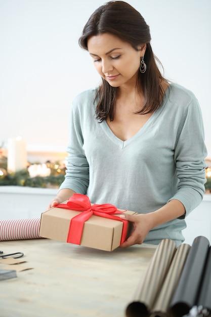 Junge frau, die weihnachtsgeschenke einwickelt Kostenlose Fotos