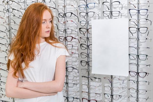 Junge frau, die weißes leeres papier im optikshop betrachtet Kostenlose Fotos