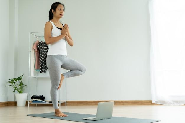 Junge frau, die yoga-baum-haltung zu hause tut. betrachten des laptop-bildschirms, gesundes lebensstilkonzept Premium Fotos