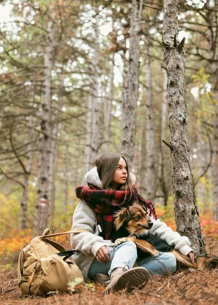 Junge frau, die zeit zusammen mit ihrem hund draußen verbringt Kostenlose Fotos