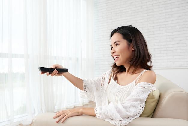 Junge frau, die zu hause auf sofa turning on tv sitzt Kostenlose Fotos