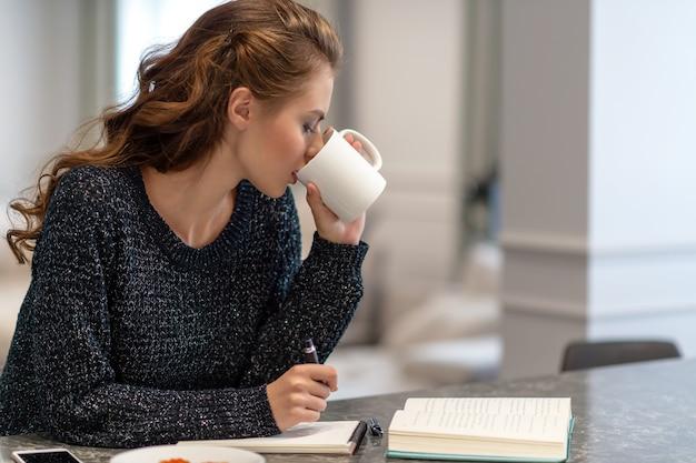 Junge frau, die zu hause mit notizblock in der küche arbeitet. sie trinkt kaffee. geschäftsideen. zu hause studieren und arbeiten. Kostenlose Fotos