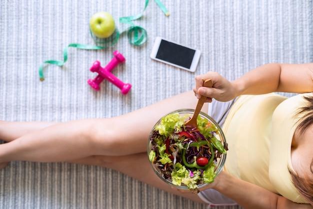 Junge frau, die zu hause selbst gemachten gesunden salat isst Premium Fotos