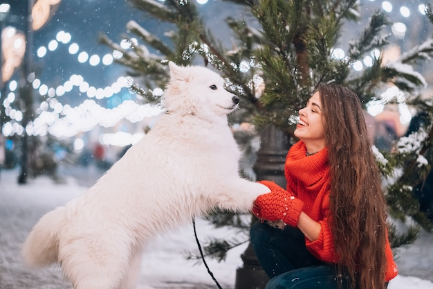 Junge frau duckte sich neben einem hund auf einer winterstraße Kostenlose Fotos