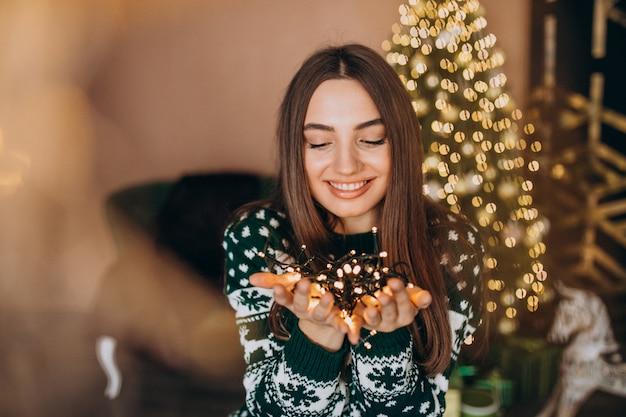 Junge frau durch den weihnachtsbaum mit weihnachtsglühenden lichtern Kostenlose Fotos