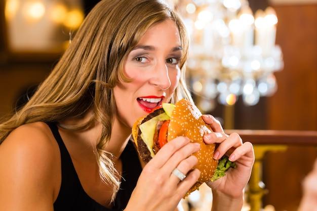 Junge frau, ein gourmetrestaurant, isst einen hamburger, sie verhält sich unkorrekt Premium Fotos