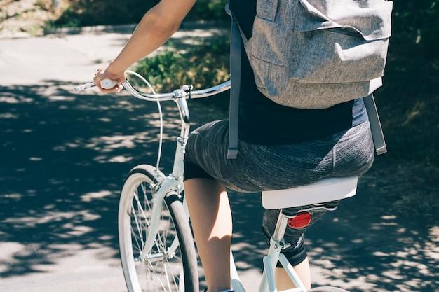 Junge frau fährt fahrrad im sommer mit einem rucksack Premium Fotos