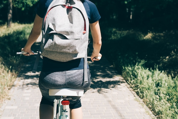 Junge frau fährt fahrrad mit einem rucksack im sommer Premium Fotos
