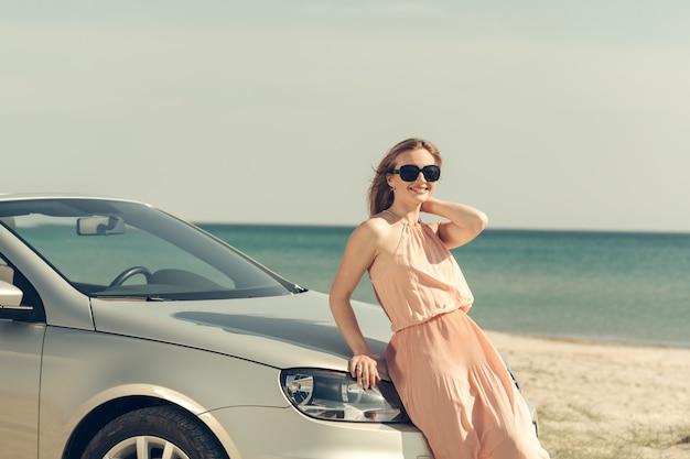 Junge frau fahren ein auto am strand Premium Fotos