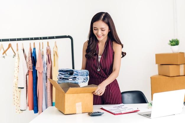 Junge frau freiberufler arbeiten sme geschäft online-shopping und verpackung kleidung mit pappkarton zu hause - Premium Fotos