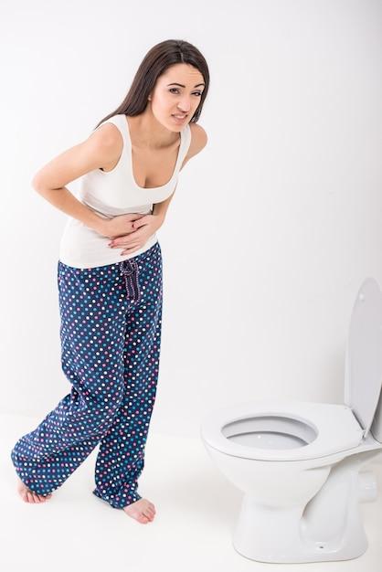 Junge frau fühlt sich schlecht in der toilette. Premium Fotos