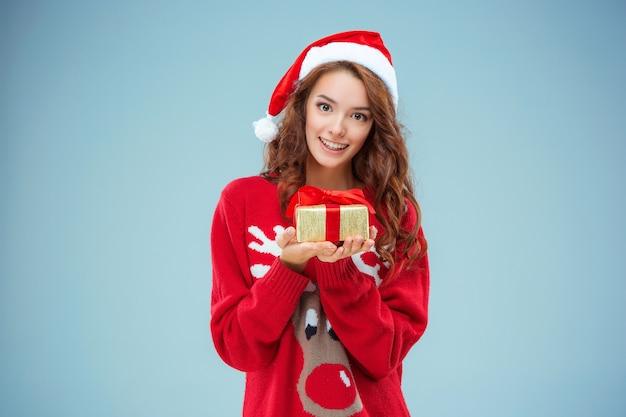 Junge frau gekleidet in weihnachtsmütze mit einem weihnachtsgeschenk Kostenlose Fotos