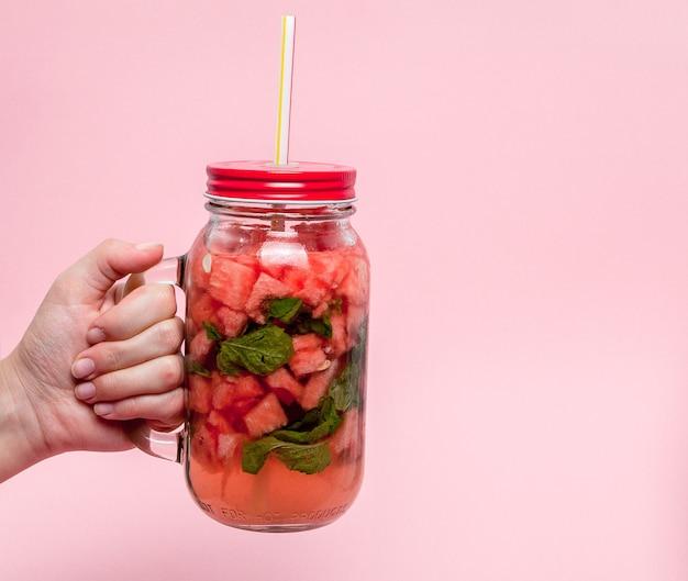 Junge frau hände, die frisch gepresste wassermelonenlimonade von zitrusfrüchten halten. Premium Fotos